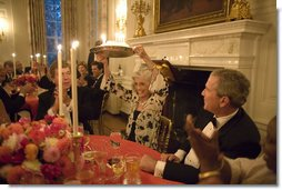 President George W. Bush watches Eunice Kennedy Shriver holding up a birthday cake during a dinner honoring her 85th birthday in the State Dining Room of the White House, Monday, July 10, 2006. Mrs. Shriver founded the Special Olympics in 1968.  White House photo by Paul Morse