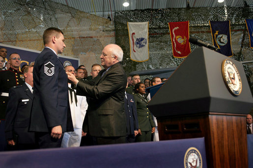 Vice President Dick Cheney pins the Purple Heart Medal onto Master Sergeant Henry G. Christle, Jr., Monday, July 10, 2006, during a rally for the Michigan National Guard and Joint Services at Selfridge Air National Guard Base in Harrison Township, Mich. Master Sergeant Christle was wounded in action on March 23, 2004 while serving as a Special Operations Weather Team Forecaster and Observer assigned to the Combined Joint Special Operations Task Force 180, Afghanistan. White House photo by David Bohrer