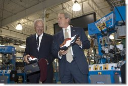 President George W. Bush holds up red, white and blue shoes presented to him by CEO John Stollenwerk during his visit to the Allen-Edmonds Shoe Corporation in Port Washington, Wis., Tuesday, July 11, 2006. White House photo by Kimberlee Hewitt