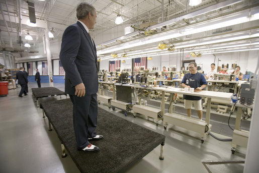 "President George W. Bush shows off his new red, white and blue shoes that were presented to him during his visit to the Allen-Edmonds Shoe Corporation in Port Washington, Wis., Tuesday, July 11, 2006. ""I'm thrilled with my new shoes,"" said the President to the press. ""I wish I had them on the Fourth of July."" White House photo by Kimberlee Hewitt"