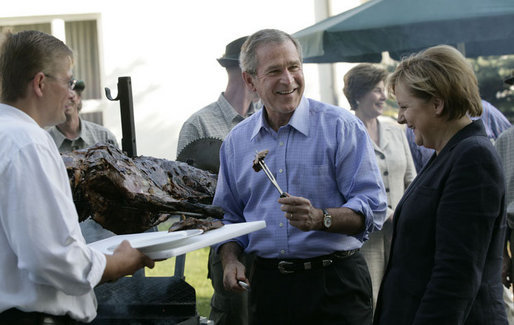 President George W. Bush enjoys a bit of barbeque Thursday, July 13, 2006, as he joins Chancellor Angela Merkel for a barbeque in Trinwillershagen. The President and Mrs. Laura Bush are scheduled to depart Germany Friday for St. Petersburg, Russia. White House photo by Eric Draper