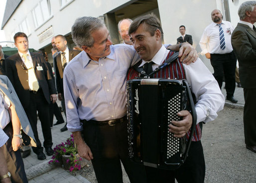 President George W. Bush puts his arm around an accordian player Thursday, July 13, 2006, after an evening barbeque in Trinwillershagen, Germany, hosted by Chancellor Angela Merkel. White House photo by Eric Draper