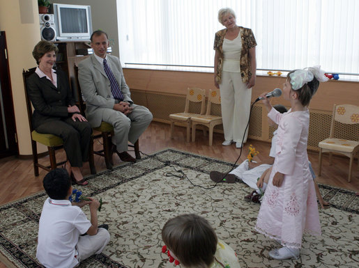 During a tour of the Pediatric HIV/AIDS Clinic Center of Russia, Mrs. Laura Bush and Dr. Evgeny Voronin listen to Gayla, a patient, perform in the Music Room Friday, July 14, 2006, in St. Petersburg, Russia. Music instructor Valentina Leontieva looks on. White House photo by Shealah Craighead