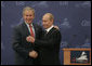 President George W. Bush and President Vladimir Putin exchange handshakes Saturday, July 15, 2006, after a joint press availability at the International Media Center in the Konstantinovsky Palace Complex, site of the G8 Summit in Strelna, Russia. White House photo by Paul Morse