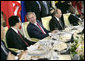 President George W. Bush talks with Chinese President Hu Jintao, left, during a luncheon with world leaders during the G8 Summit at the Konstantinovsky Palace Complex Monday, July 17, 2006 in Strelna, Russia. Also pictured is Russian President Vladimir Putin, and South African President Thabo Mbeki, far-right. White House photo by Eric Draper