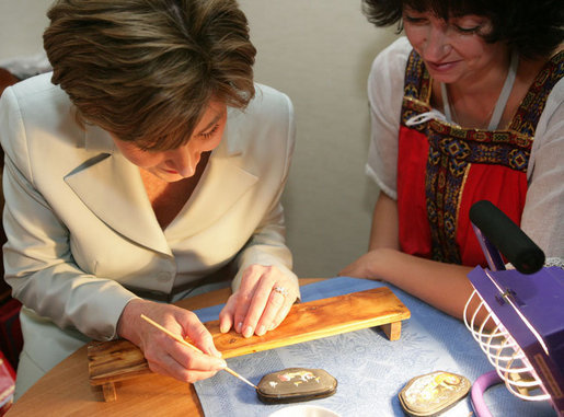 Mrs. Laura Bush receives instruction in arts and crafts Monday, July 17, 2006, during an exhibit at the Baltic Star Hotel on the grounds of the Konstantinovsky Palace Complex in Strelna, Russia, site of the G8 Summit that ended Monday. White House photo by Shealah Craighead