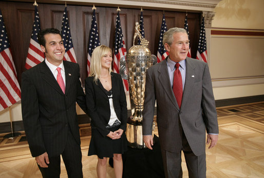 President George W. Bush meets with Sam Hornish Jr., the 2006 winner of the Indianapolis 500, and his wife, Crystal Hornish, as they stand next to the 500 race Borg-Warner Trophy Tuesday, July 18, 2006, at the Eisenhower Executive Office Building in Washington. White House photo by Eric Draper