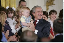 "President George W. Bush holds 14-month-old Trey Jones of Cypress, Texas, following his remarks about stem cell research policy legislation in the East Room of the White House Wednesday, July 19, 2006. ""Each of these children was adopted while still an embryo, and has been blessed with the chance to grow up in a loving family,"" said the President of children sharing the stage with him. ""These boys and girls are not spare parts. They remind us of what is lost when embryos are destroyed in the name of research."" Trey Jones was first introduced to the President during a White House visit in May 2005. White House photo by Kimberlee Hewitt"