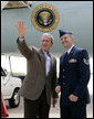 President George W. Bush meets with U.S. Air Force Tech. Sgt. Brian Webster next to Air Force One Friday, July 21, 2006, where he honored Webster with the President's Volunteer Service Award at Buckley Air Force Base in Aurora, Colo. Tech. Sgt. Webster is co-founder and treasurer of the Hearts Across the Miles, a non-profit organization to providedeployed military personnel with care packages and thank you letters. White House photo by Eric Draper