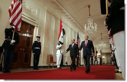"President George W. Bush and Iraqi Prime Minister Nouri al-Maliki walk through the Cross Hall to the East Room where the two leaders held a joint press conference Tuesday, July 25, 2006. ""You have a strong partner in the United States of America, and I'm honored to stand here with you, Mr. Prime Minister,"" said President Bush. ""It's a remarkable and historical moment, as far as I'm concerned, to welcome the freely elected leader of Iraq to the White House."" White House photo by Kimberlee Hewitt"