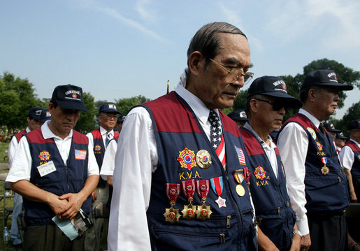 Members of the Korean War Veterans Association bow their heads during the invocation at the 2006 Korean War Veterans Armistice Day Ceremony, Thursday, July 27, 2006, at the Korean War Memorial in Washington, D.C. White House photo by David Bohrer