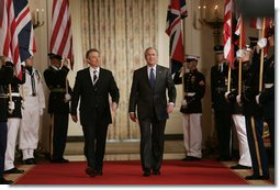 President George W. Bush is joined by Prime Minister Tony Blair of the United Kingdom as they walk through Cross Hall to the East Room of the White House Friday, July 28, 2006, to participate in a joint press availability. White House photo by Paul Morse