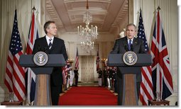 President George W. Bush is joined by Prime Minister Tony Blair of the United Kingdom as he answers a reporter's question during a joint press availability Friday, July 28, 2006, in the East Room of the White House. White House photo by Paul Morse