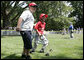 A player for the Thurmont Little League Civitan Club of Frederick Challengers of Thurmont, Md., is accompanied to first base by a South Lawn buddy Sunday, July 30, 2006, at the White House Tee Ball on the South Lawn game against the Shady Spring Little League Challenger Braves of Shady Spring W. Va. White House photo by Paul Morse