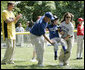 A player for the Shady Spring Little League Challenger Braves of Shady Spring W. Va., is helped around the bases Sunday, July 30, 2006, at the White House Tee Ball on the South Lawn game against the Thurmont Little League Civitan Club of Frederick Challengers of Thurmont, Md. White House photo by Paul Morse