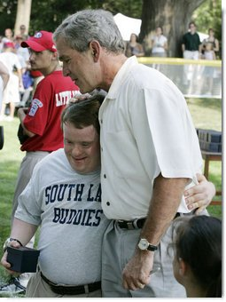 President George W. Bush embraces a South Lawn buddy volunteer Sunday, July 30, 2006, on the South Lawn of the White House at the conclusion of the Tee Ball on the South Lawn game between the Thurmont Little League Civitan Club of Frederick Challengers of Thurmont, Md., and the Shady Spring Little League Challenger Braves of Shady Spring, W. Va.  White House photo by Paul Morse
