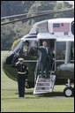 President George W. Bush waves from the steps of Marine One on the South Lawn of the White House Thursday, Aug. 3, 2006, as he departs to visit the U.S.-Mexico border patrol facilities in McAllen and Mission, Texas. White House photo by Kimberlee Hewitt
