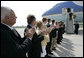 "President George W. Bush is applauded by a welcoming committee of state and local community leaders as he arrives at Austin Straubel International Airport in Green Bay, Wis., Thursday, Aug. 10, 2006. After greeting the welcoming committee President Bush spoke to reporters on the airline bombing plot uncovered in the United Kingdom, saying it is ""a stark reminder that this nation is at war with Islamic fascists who will use any means to destroy those of us who love freedom, to hurt our nation."" White House photo by Eric Draper"