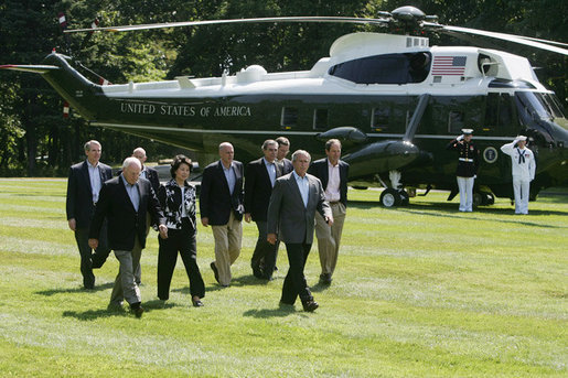 President George W. Bush leads his economic advisors past Marine One on the way to speak with reporters Friday, Aug. 18, 2006 in Camp David, Md., following their meeting on the nation's economy. President Bush said the foundation of our economy is strong and is maintaining solid growth. White House photo by David Bohrer