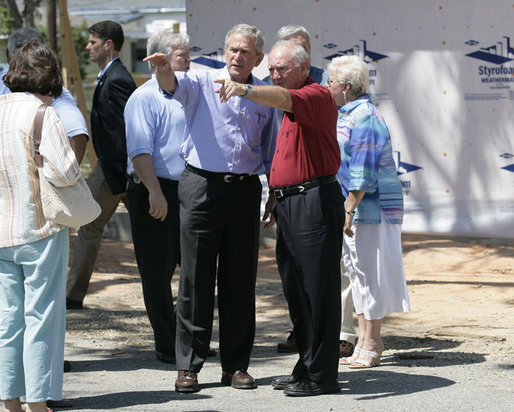 President George W. Bush is joined by Biloxi, Miss. Mayor A.J. Holloway, right, Monday, Aug. 28, 2006, during President Bush's walking tour in the same Biloxi neighborhood he visited following Hurricane Katrina in September 2005. The tour allowed President Bush the opportunity to assess the progress of the area's recovery and rebuilding efforts following the devastating hurricane. White House photo by Eric Draper