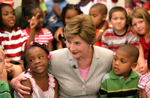 Mrs. Laura Bush embraces two students Monday, Aug. 28, 2006, as she meets and speaks with members of the Gorenflo Elementary School first grade class in their temporary portable classroom at the Beauvoir Elementary School in Biloxi, Miss. The students, whose school was damaged by Hurricane Katrina, are sharing the facilities of the Beauvoir school until their school's renovations are complete. White House photo by Shealah Craighead
