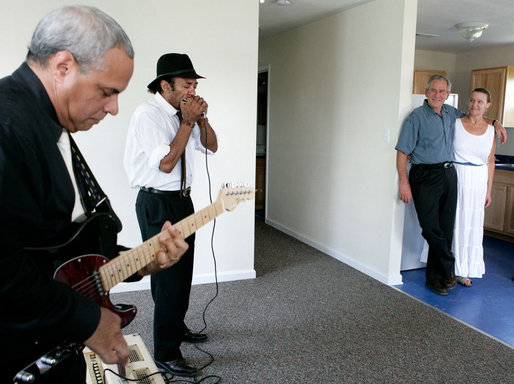President George W. Bush stands with Polly Noble as they listen Tuesday, Aug. 29, 2006, to J.D. Hill on his harmonica and guitarist Charlie Moore during a visit to Musicians' Village in New Orleans' 9th Ward. The President and Laura Bush hosted a lunch with volunteers from Habitat for Humanity in appreciation of their work on the site for displaced New Orleans musicians. White House photo by Eric Draper