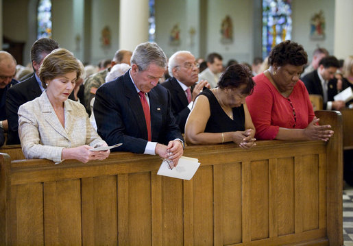 President George W. Bush and Laura Bush bow their heads in prayer Tuesday, Aug. 29, 2006, during a service at New Orleans' St. Louis Cathedral commemorating the first anniversary of Hurricane Katrina. Joining them are Ethel Williams, a 9th Ward resident, and her sister, Wanda. White House photo by Eric Draper