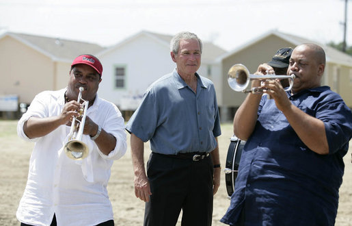President George W. Bush is greeted by the New Birth Brass Band as he arrives Tuesday, Aug. 29, 2006, at the Habitat for Humanity's Musician's Village in New Orleans' 9th Ward, where he had lunch with volunteers and local residents. The Village will consist of 81 Habitat-constructed homes for displaced New Orleans musicians. White House photo by Eric Draper