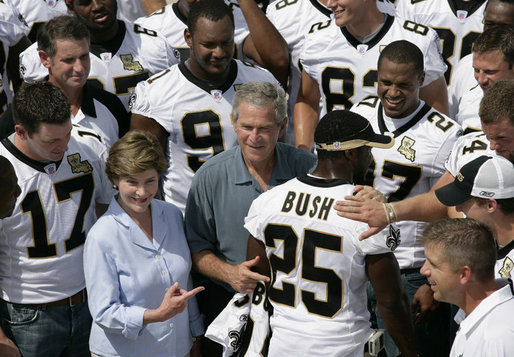 President George W. Bush and Laura Bush are surrounded by members of the New Orleans Saints football team Tuesday, Aug. 29, 2006, as they point out the name of Saints star rookie running back Reggie Bush, when the team met President Bush at the New Orleans Airport to pose for a team photo. White House photo by Eric Draper