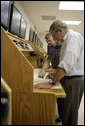President George W. Bush looks over navigational charts of the Chesapeake Bay with student, Andrew Ashworth, direct left and John Mason, President of Seafareres International Union,far left, during a tour of the Paul Hall Center for Maritime Training and Education on Monday, September 4, 2006. White House photo by Kimberlee Hewitt
