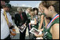 President George W. Bush signs autographs as he meets with members of the 2006 Little League Softball World Series Champions at Bishop International Airport before departing Flint, Mich. White House photo by Kimberlee Hewitt