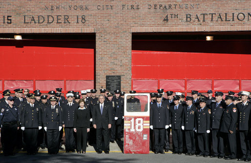 President George W. Bush and Laura Bush stand with New York City First Responders at the Fort Pitt Firehouse for a moment of silence Monday, September 11, 2006, in New York City to commemorate the fifth anniversary of the September 11th terrorist attacks. Also pictured is a door from Ladder 18, which was destroyed in the collapse of the World Trade Center. White House photo by Kimberlee Hewitt