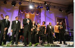 President George W. Bush stands with performers on stage in the East Room Thursday night, Sept. 14, 2006, as he offers closing remarks to guests at the Thelonious Monk Institute of Jazz dinner at the White House. White House photo by Shealah Craighead