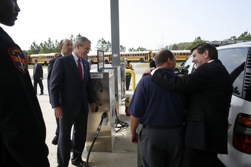President George W. Bush observes an alternative fueling demonstration with Hoover Police Department Officer Reggie Parker, center, being embraced by Alabama Governor Bob Riley, Thursday, Sept. 28, 2006, during President Bush's visit to the Hoover Public Safety Center in Hoover, Ala. The city has just opened an alternative fueling station to provide E85 (ethanol) and biodiesel fuels for public agency vehicles. White House photo by Paul Morse