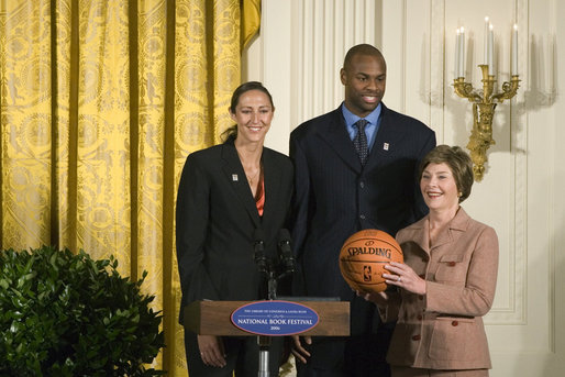 Mrs. Laura Bush stands with Ruth Riley, Detroit Shock WNBA player, left, and Brendan Haywood, Washington Wizards NBA player, after receiving the NBA Cares award Saturday, September, 30, 2006, during the National Book Festival opening ceremony in the East Room of the White House. White House photo by Shealah Craighead