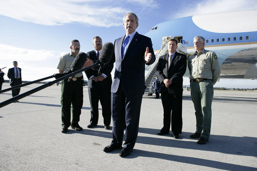 "President George W. Bush stands with California forestry officials as he delivers a statement Tuesday, Oct. 3, 2006, at Los Angeles International Airport regarding the state's wildfires. The President told the crowd, ""I really want to thank the brave firefighters who risk their lives on a daily basis to contain the fires."" White House photo by Eric Draper"