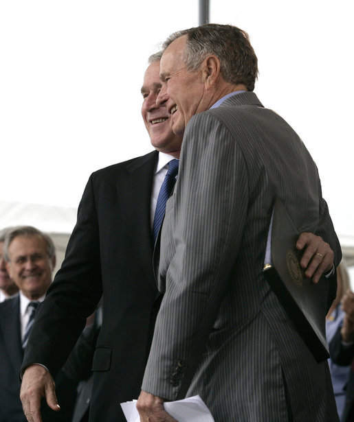 President George W. Bush hugs his father, Former President George H. W. Bush, after delivering remarks at the Christening Ceremony for the George H.W. Bush (CVN 77) in Newport News, Virginia, Saturday, Oct. 7, 2006. White House photo by Eric Draper