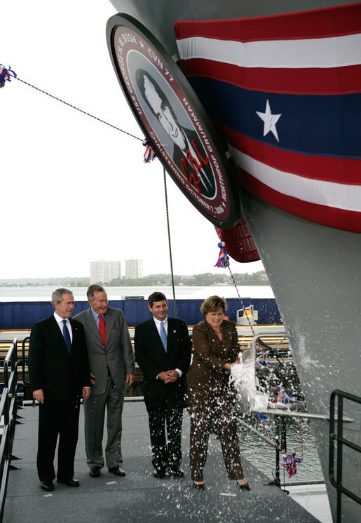 President George W. Bush joins his father, Former President George H. W. Bush and Northrop Grumman President Mike Petters, as his sister Doro Bush Koch breaks the bottle to christen the George H.W. Bush (CVN 77) in Newport News, Virginia, Saturday, Oct. 7, 2006. White House photo by Eric Draper