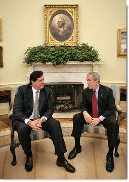 "President George W. Bush talks with President Alan Garcia of Peru in the Oval Office Tuesday, Oct. 10, 2006. ""We talked about world issues, we talked about issues regarding South America and Central America, and we talked about our bilateral relations,"" said President Bush in his remarks to the press. ""The central issue facing us right now is the passage of a free trade agreement.""  White House photo by Eric Draper"