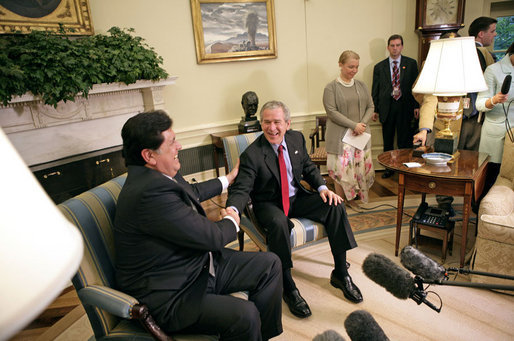 "President George W. Bush laughs with President Alan Garcia of Peru during a meeting with the press in the Oval Office Tuesday, Oct. 10, 2006. ""We see our role as a country in terms of helping strengthen democracy and achieving friendship without threat in our region,"" said President Garcia. ""And in this regard, Peru will continue to work towards the democratization of Latin America."" White House photo by Eric Draper"