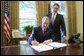 With Sen. Bill Frist (R-Tenn.) looking on, President George W. Bush signs into law S. 3728, the North Korea Nonproliferation Act of 2006, Friday, Oct. 13, 2006, in the Oval Office. White House photo by Eric Draper
