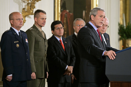 "President George W. Bush speaks during the signing of S. 3930, the Military Commissions Act of 2006, Tuesday, Oct. 17, 2006, in the East Room. ""It is a rare occasion when a President can sign a bill he knows will save American lives. I have that privilege this morning,"" said President Bush. Pictured in the background are, from left, Deputy Director of National Intelligence Michael Hayden; General Peter Pace, Chairman of the Joint Chiefs of Staff; Attorney General Alberto Gonzales; Defense Secretary Donald Rumsfeld and Vice President Dick Cheney. White House photo by Paul Morse"