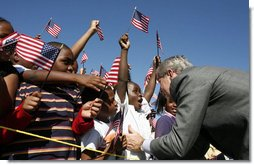 President George W. Bush greets flag-waving students at the Waldo C. Falkener Elementary School Wednesday, Oct. 18, 2006, in Greensboro, N.C., where he delivered remarks on the No Child Left Behind Act.  White House photo by Paul Morse