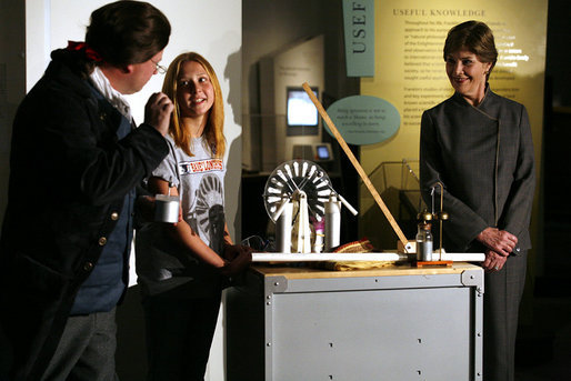 Mrs. Laura Bush watches as David Temple, actor portraying Benjamin Franklin, performs a demonstration related to static electricity at the Houston Museum of Natural Science, Wednesday, October 18, 2006, with the help of a 6th grade student from the Baines Middle School in Houston, TX. White House photo by Shealah Craighead