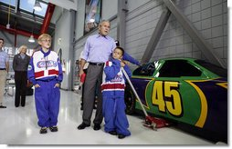 "President George W. Bush gets a close-up view of the 45 car Wednesday, Oct. 18, 2006, at Victory Junction Gang Camp, Inc. with Will ""Cheese"" Kwapil, 12, left, who suffers from a congenital heart defect, and Pauly Rader, 9, who has a brain tumor. The camp, founded by Kyle and Pattie Petty, serves children primarily from North Carolina, South Carolina and Virginia with chronic medical conditions or serious illnesses.  White House photo by Paul Morse"