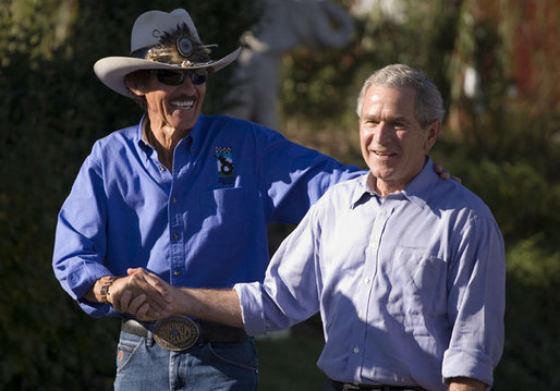 President George W. Bush enjoys a moment with NASCAR racing champion Richard Petty during a visit Wednesday, Oct. 18, 2006, to the Victory Junction Gang Camp, Inc., in Randleman, N.C. The center was founded by Petty's son, Kyle, and Kyle's wife, Pattie, in memory of their son, Adam, a fourth-generation NASCAR driver killed during practice in 2000. White House photo by Paul Morse