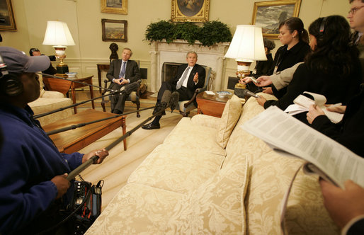 President George W. Bush speaks to reporters as he sits with NATO Secretary-General Jaap de Hoop Scheffer in the Oval Office Friday, Oct. 27, 2006. White House photo by Kimberlee Hewitt
