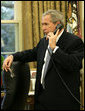 President George W. Bush makes a telephone call Friday, Oct. 27, 2006, to Tom Tidwell, Deputy Regional Forester, about the deaths Thursday of four firefighters in a Southern California wildfire. The firefighters were killed while battling the Esperanza fire near Palm Springs. White House photo by Paul Morse