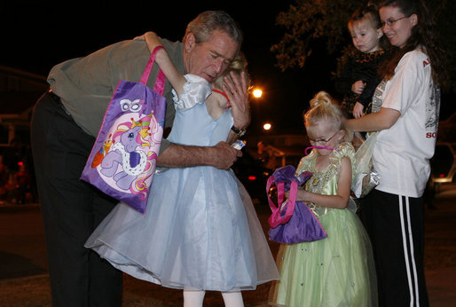 President George W. Bush hugs a trick-or-treater Tuesday, Oct. 31, 2006, during a Halloween visit to a housing development on base at Robins Air Force Base, Ga. White House photo by Paul Morse