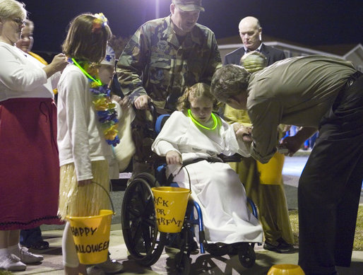 President George W. Bush greets a trick-or-treater Tuesday, Oct. 31, 2006, during an unexpected stop on base at Robins Air Force Base, Ga. White House photo by Paul Morse